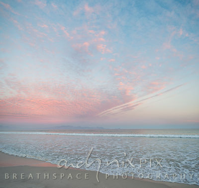 A seascape in soft pastel light; pink clouds in a pale blue sky, white waves washing up a beach from a silver sea.