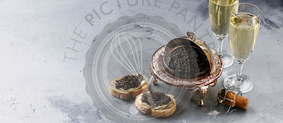 Black caviar in silver bowl, sandwiches and champagne on gray concrete background copy space