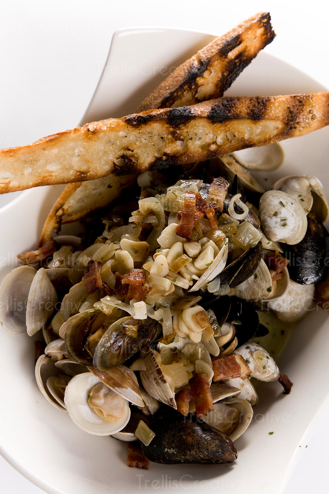 Bowl of steamed mussels and clams with leeks and pancetta