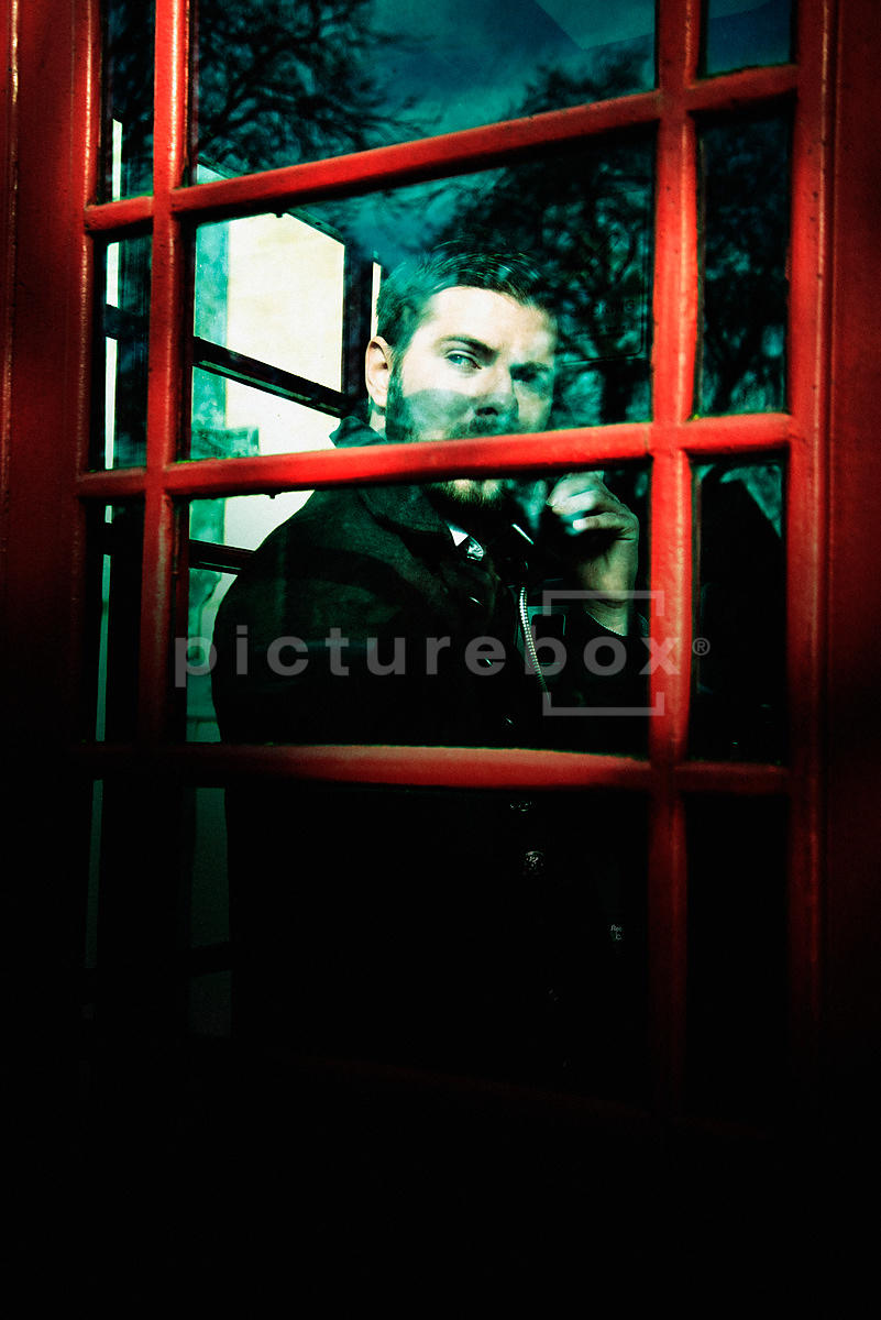An atmospheric image of a man looking out of the window from inside an old English telephone box.