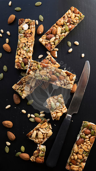 Nut and Seed Bars with a knife on a black blackground.