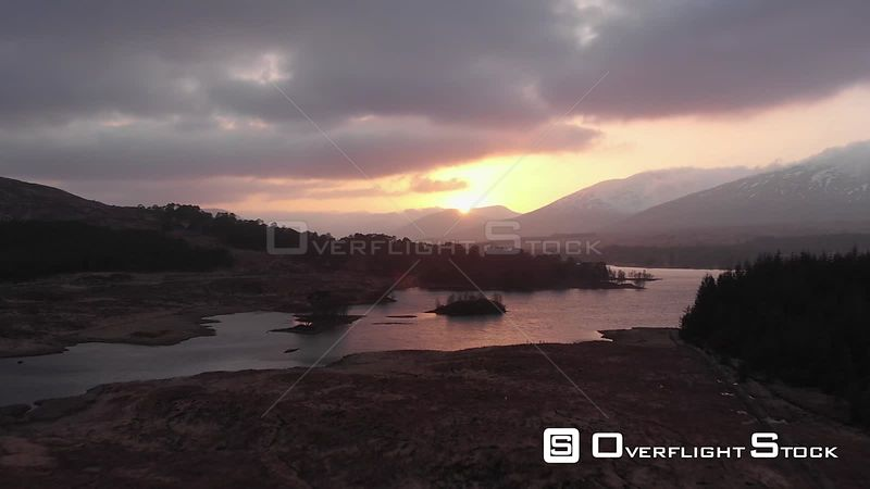 Aerial drone shot of sunset behind mountains, Highlands of Scotland