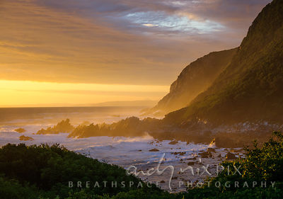 Golden orange sunset light illuminates wild waves crashing against sharp, jagged rocks on a steep, wild coast.