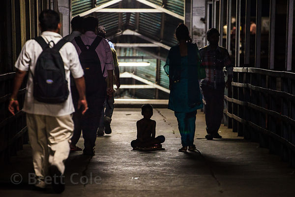 A boy begs for money in a hallway at the Bandra Railway Station, Mumbai, India.