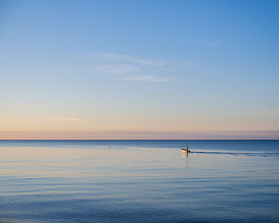 A fisherman leaves to tend his pots early in the morning on a calm sea at Budliegh Salterton, Devon, UK