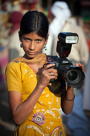 An Indian girl with a large professional camera at the Pushkar Camel Mela, Pushkar, India. She was acting as an assistant to ...