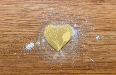 Heart shaped marzipan on sugar, and wooden background