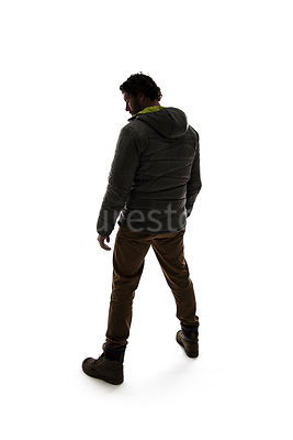 A man in outdoor clothing from behind, in silhouette – shot from eye level.