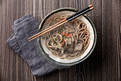 Asian noodles Yakisoba with beef and oyster mushrooms in bowl on gray wooden background