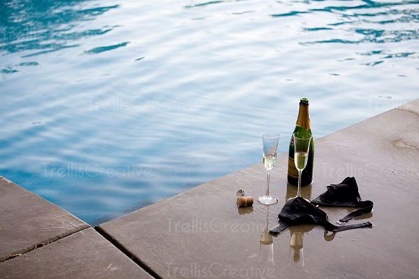 A woman's bikini top, two glasses and a bottle of champagne poolside