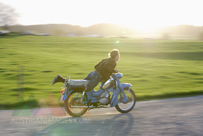 Germany, Bavaria, Mature woman riding old moped of 1960s