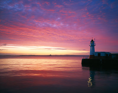 Spectacular sunrise over Mount's Bay with the lighthouse at the end of Newlyn harbour wall.
