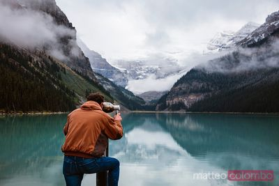 Man looking through binoculars, Lake Louise, Canada