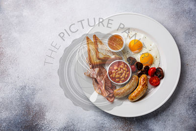 English breakfast with fried egg, sausage, bacon, beans and toast on white background copy space