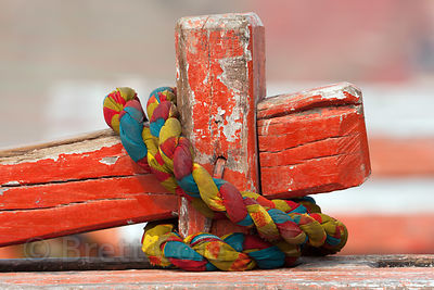 Colorful rope on a weathered orange fishing boat on the Ganges River, Varanasi, India.