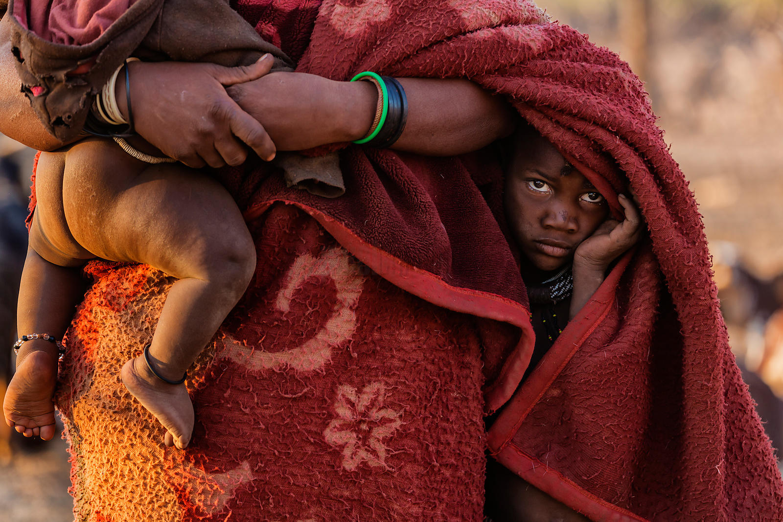 Portrait of a Young Himba Boy Peeping out from the Folds of his Mother's Blanket