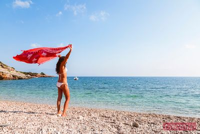 Woman with sarong on beach. Zakynthos, Greek Islands, Greece