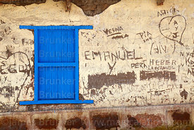 Blue wooden shutters and graffiti on adobe wall of house, Putre, Region XV, Chile