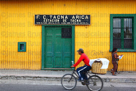 Cyclist riding past entrance to terminal building of Tacna to Arica railway , Tacna , Peru