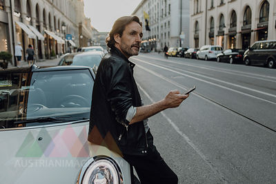 Mature man leaning on car, holding smartphone, Munich, Bavaria, Germany