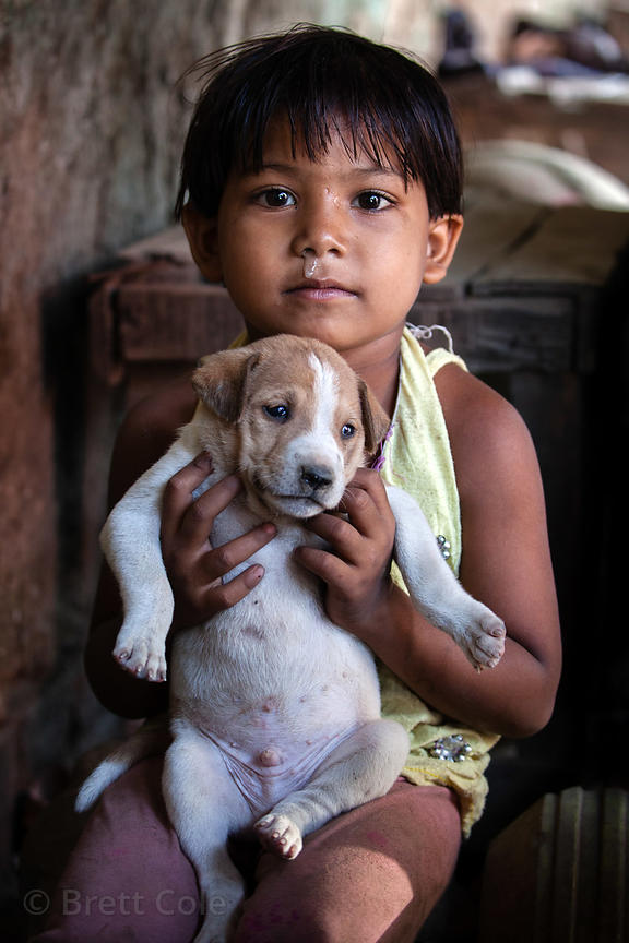 A boy holds a stray dog puppy on Strand Road, Kolkata, India.