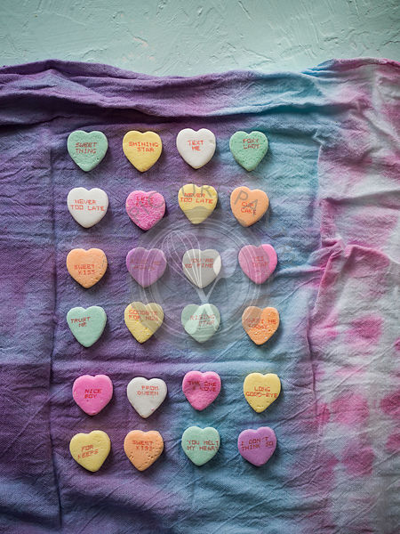 Colorful, overhead image of conversation love hearts organized on a rainbow linen on a mint green surface.