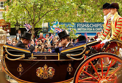 Prince William and Prince Harry in and open Carriage tipping their top hats to each other as they pass a fish and chip stall ...