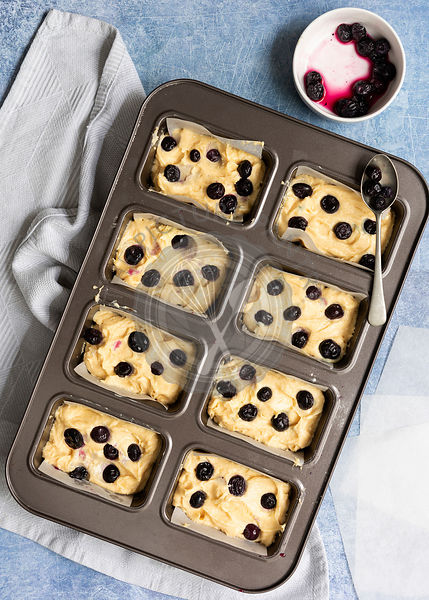Cake batter covered with blueberries in an individual mini loaf baking tin.