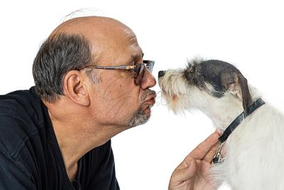 Man Giving Kiss to Shaggy Terrier Crossbreed Dog