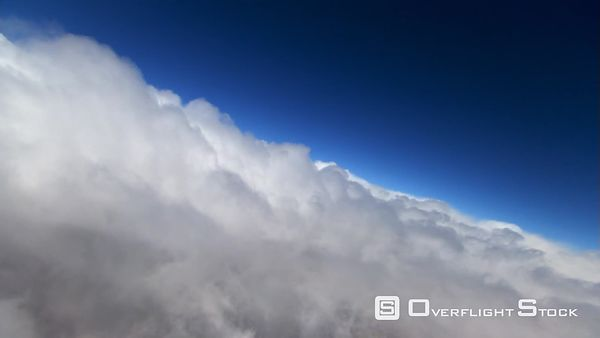 Veering flight over puffy clouds, precipitation on lens