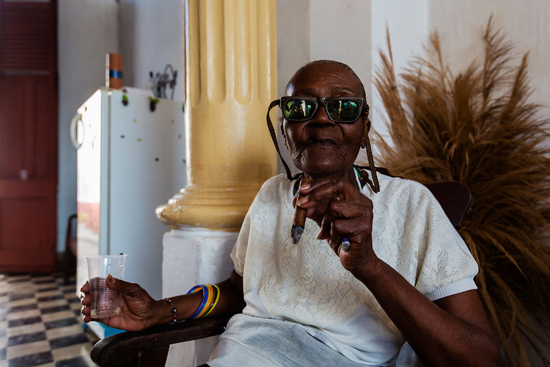 Elderly Woman with Dark Glasses Enjoying a Cigar