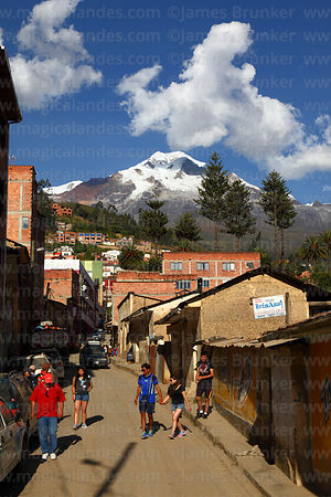 Group of friends walking along street in Sorata, Mt Illampu in background, Bolivia