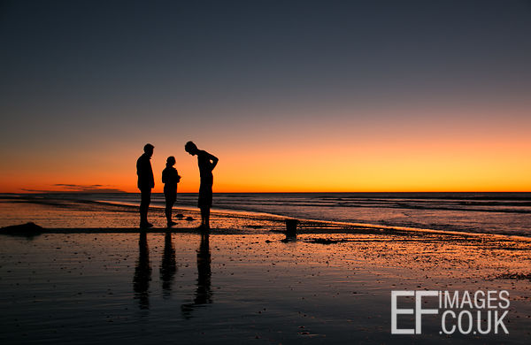 Three Firends On A Beach At Sunset