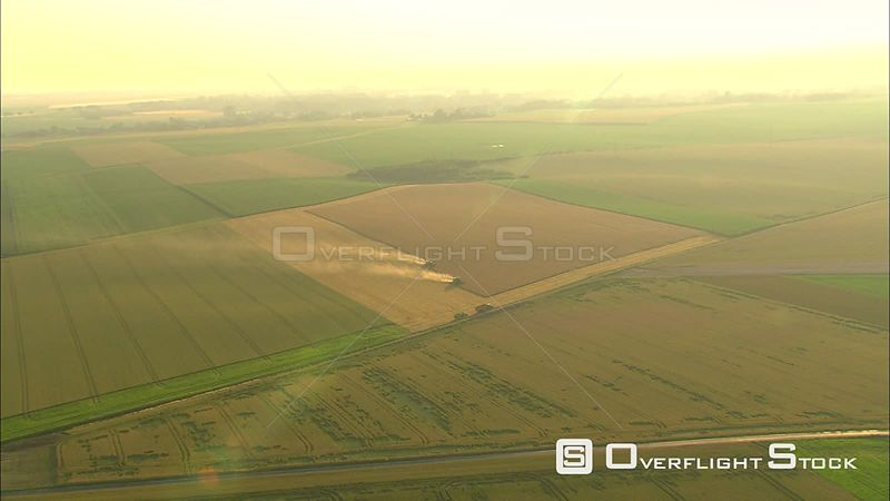 Flying over Belgian farmland and farm equipment at work in a golden field