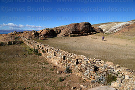 Inca wall and tourist visiting the Sacred Rock / Titikala in Sanctuary area near Chincana ruins, Sun Island, Lake Titicaca, B...