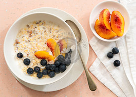 Oats, peach slices, blueberries and milk in a bowl for breakfast.