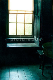 An atmospheric image of the light coming through an old window, into an Victorian / Elizabethan room.