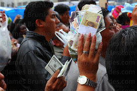A woman holds up miniature bank notes to be blessed with holy water by priests outside San Francisco church, Alasitas festiva...