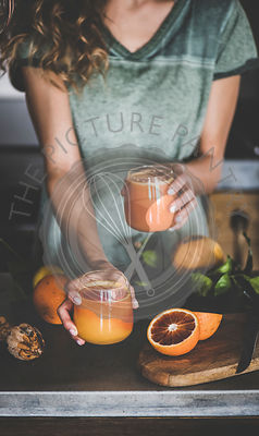 Woman holding glasses with fresh blood orange juice