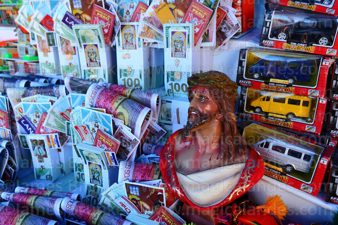Miniature money bundles, toy cars and statue of crucified Christ for sale in market for Alasitas festival, Puno, Peru
