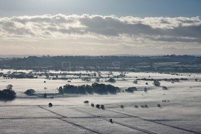 View south over the Somerset Levels from Walton Hill on a misty winter evening with snow on the ground. View includes Butleig...
