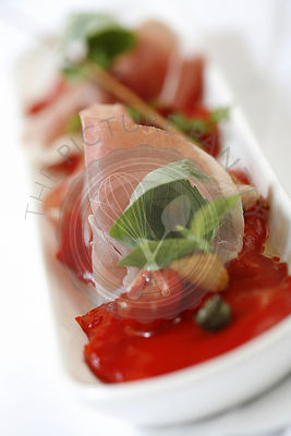 Salad of roasted red peppers with parma ham, olive crisps and basil.