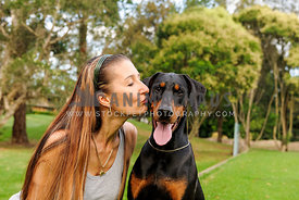 Female with long brown hair kissing Doberman