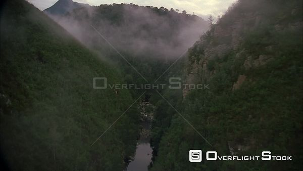 Aerial through a lush green misty river gorge. Eastern Cape South Africa