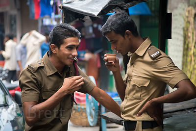 Police officers chat over chai tea during the Durga Puja festival, Newmarket, Taltala, Kolkata, India