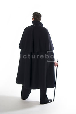 An image of a Victorian man in a cloak, standing, from behind.