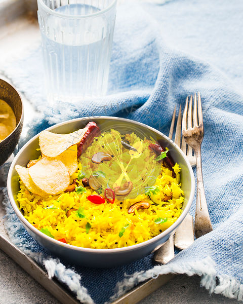 Lemon rice served in a grey bowl with potato crisps and water