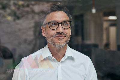 Portrait of smiling man with stubble behind windowpane wearing white shirt and glasses
