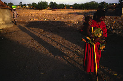 Ghana - Arigu - Asumpaheme, who is blind, goes to collect water at a water hole. Her grandchild is strapped to her back.