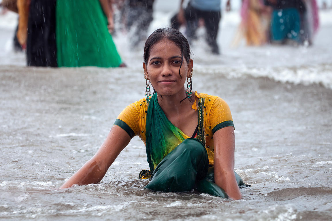 A woman in a sari swims in the Arabian Sea in monsoon rains, Juhu Beach, Mumbai, India.